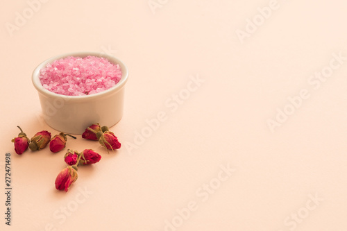 Spa aroma therapy. Closeup of pink bath salt in white bowl and red rose flower buds. Peach background. Copy space.