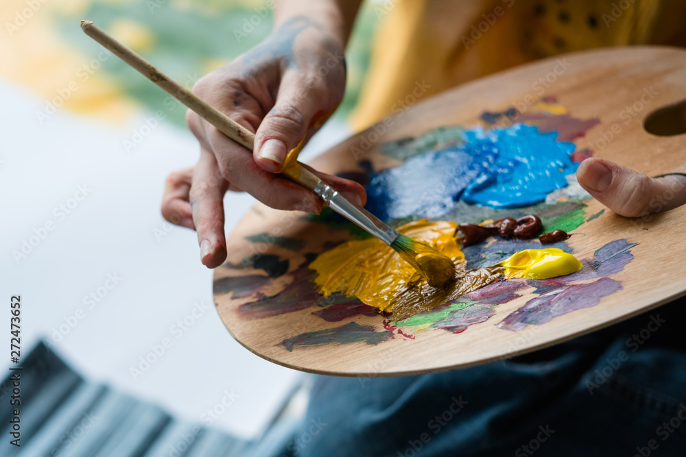 Fototapety, obrazy: Fine art school. Closeup of artist hands holding wooden palette, mixing acrylic paint with brush.