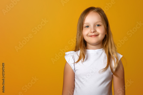 Obraz Portrait of a cute little girl on a yellow background. A child blonde is smiling and looking at the camera. Copy space. - fototapety do salonu