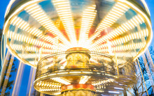 Carousel Moving And Unfocused Effect Of A Merry-go-round With Colorful Lights At Dusk At An Amusement Park