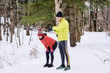 Couple relaxing after running in winter forest.