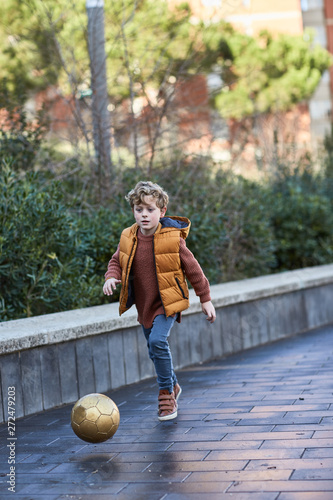 Six year old boy playing football in a city park