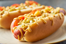 Two Juicy Hot Dogs Close-up On Dish Over Stone Table