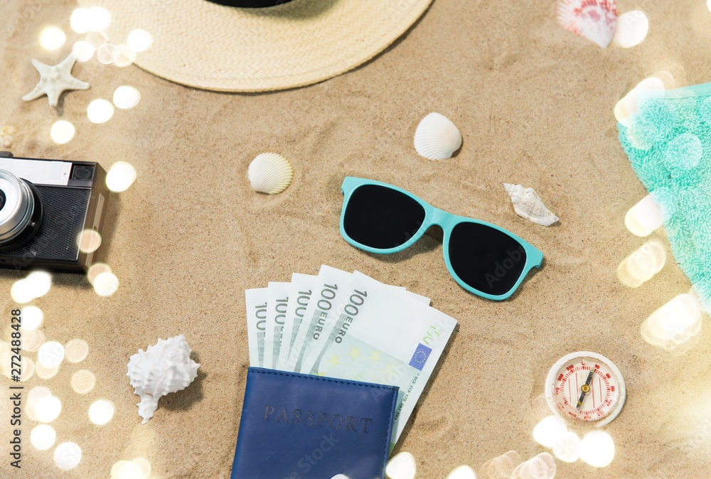 Fototapety, obrazy: vacation, travel and tourism concept - vintage camera, money in passport, hat and sunglasses on beach sand