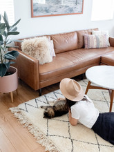 Young Woman Laying On Living Room Rug With Cat