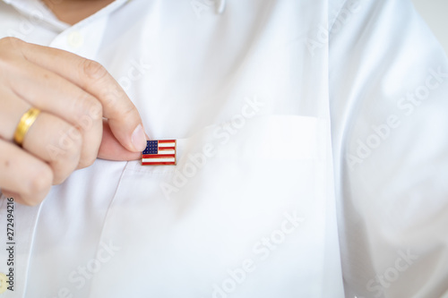 Close up of man hand holding United State of America nation flag pin on white shirt flag Wallpaper Mural