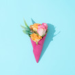 canvas print picture - Pink ice cream cone with colorful flowers on pastel blue background. Minimal summer flat lay composition.