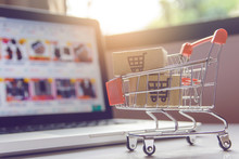 Shopping Online. Parcel Or Cardboard Boxes With A Shopping Cart Logo In A Trolley On A Laptop Keyboard. Shopping Service On The Online Web. Offers Home Delivery.