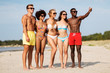 Leinwandbild Motiv friendship, summer holidays and people concept - happy friends hugging on beach