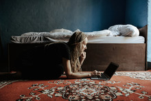 Young Woman Using Laptop In Be...