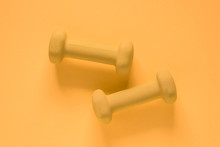 Fitness Equipment With Womens Yellow Weights/ Dumbbells Isolated On A Yellow Background With Copyspace