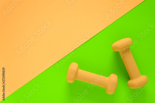 Fitness equipment with womens yellow weights/ dumbbells isolated on a lime green and yellow pink background with copyspace