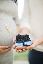 Expecting Parents Holding Little Baby Boy Shoes