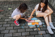 Girls Drawing Colorful Hearth Shape With Chalks