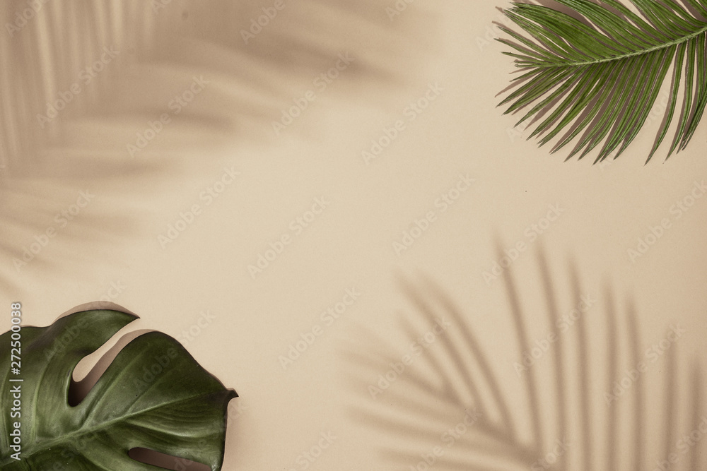 Fototapety, obrazy: Top view of green tropical leaves and shadow on sand color background. Flat lay. Minimal summer concept with palm tree leaf. Creative copyspace.
