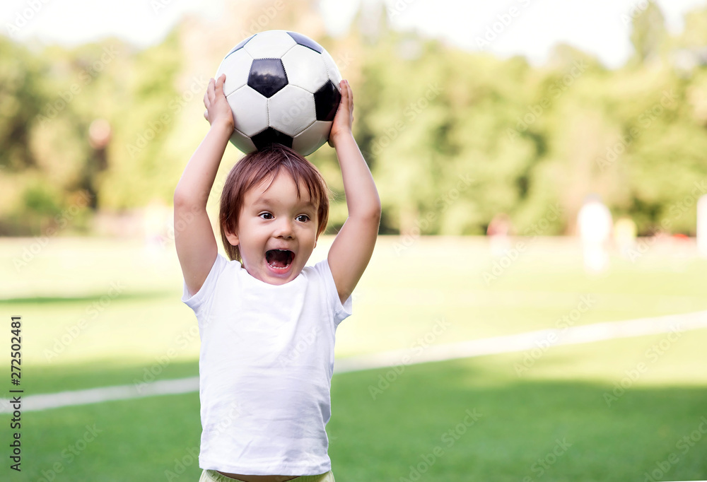 Fototapety, obrazy: Excited little toddler boy playing football on soccer field outdoors: the kid is holding ball above head and shouting ready to throw it. Active childhood and sports passion concept