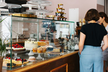 Pastry Shop Customers Standing Next To Cake Display