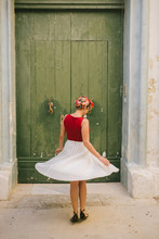 Girl In A Vintage Dress Spinning In Front Of A Wooden Doors
