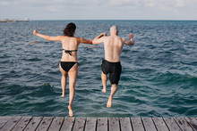 Couple Jumping Into The Ocean