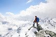 canvas print picture - mountaineer on the top of a mountain in the background of the landscape of snowy mountains