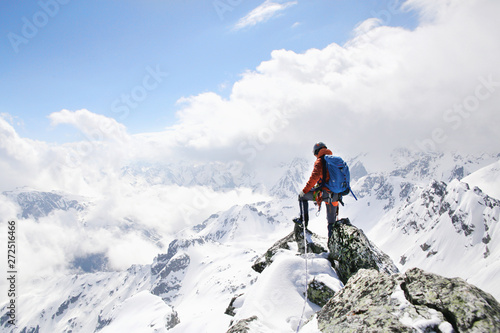 Vászonkép mountaineer on the top of a mountain in the background of the landscape of snowy