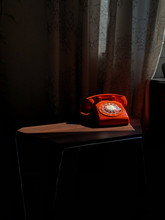 Old Orange Rotary Phone In A Sunbeam On An End Table.