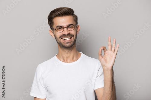 Valokuva  Happy guy gesturing ok sign smiling looking at camera
