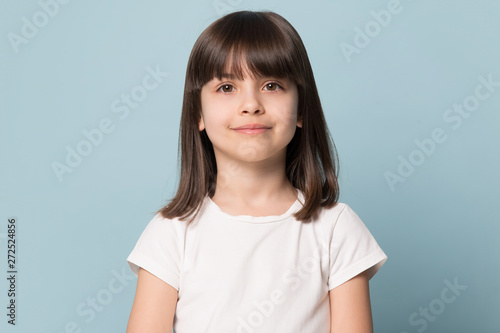 Little girl looking at camera isolated on blue studio background Fototapeta