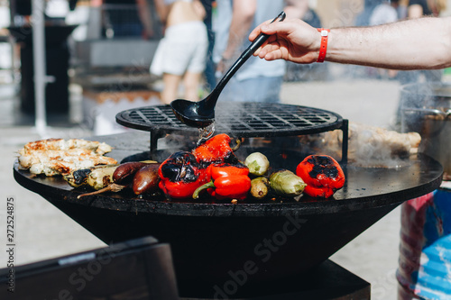 Photo Stands Grill / Barbecue delicious vegetables grilling in open grill, outdoor kitchen. food festival in city. tasty food peppers zucchini roasting on basket, food-court. summer picnic
