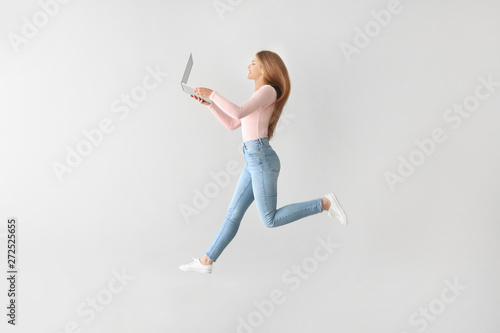 Jumping young woman with laptop on light background