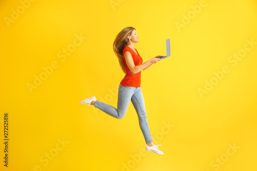 Beautiful jumping woman with laptop on color background