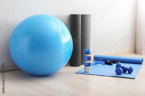 Photo Set of sports equipment with fitness ball and bottle of water near light wall