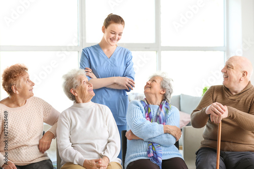 Young caregiver with group of senior people in nursing home Poster Mural XXL