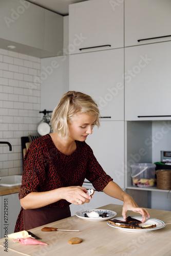 Woman making Halloween cookies in kitchen