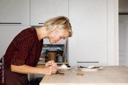 Woman icing cookies at table in kitchen