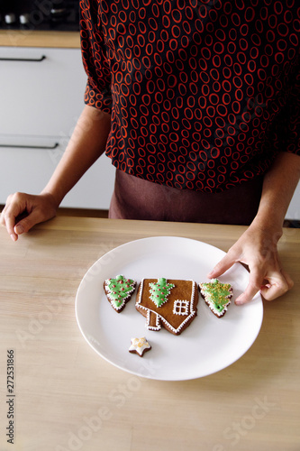 Crop woman with decorated cookies on plate