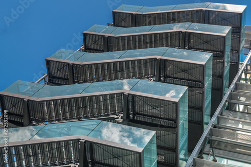Valokuvatapetti Business building with metal emergency ladder / fire escape in modern office buildings with repeating structure and reflected sky and clouds