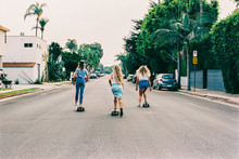 Three Young Anonymous Girls Skateboarding In Venice California