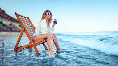 Fototapeta Pretty woman relaxing on a lounger beach and drinks soda water