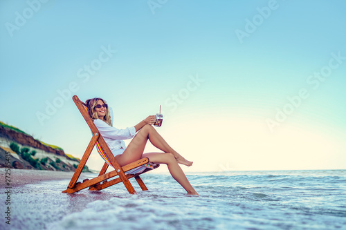 Photo  Pretty woman relaxing on a lounger beach and drinks soda water