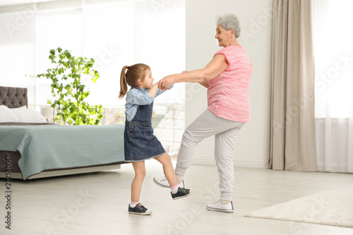Cute girl and her grandmother dancing at home - 272540047