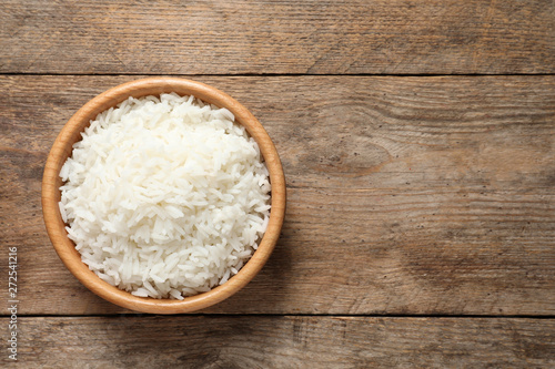 Photo Bowl of delicious rice on wooden table, top view with space for text
