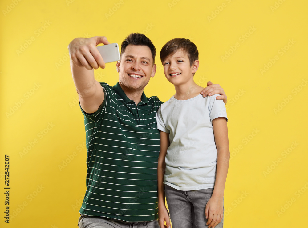 Fototapety, obrazy: Dad and his son taking selfie on color background