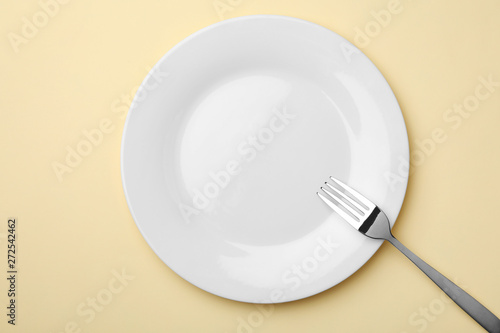 Fotografie, Obraz  Empty plate and fork on color background, flat lay