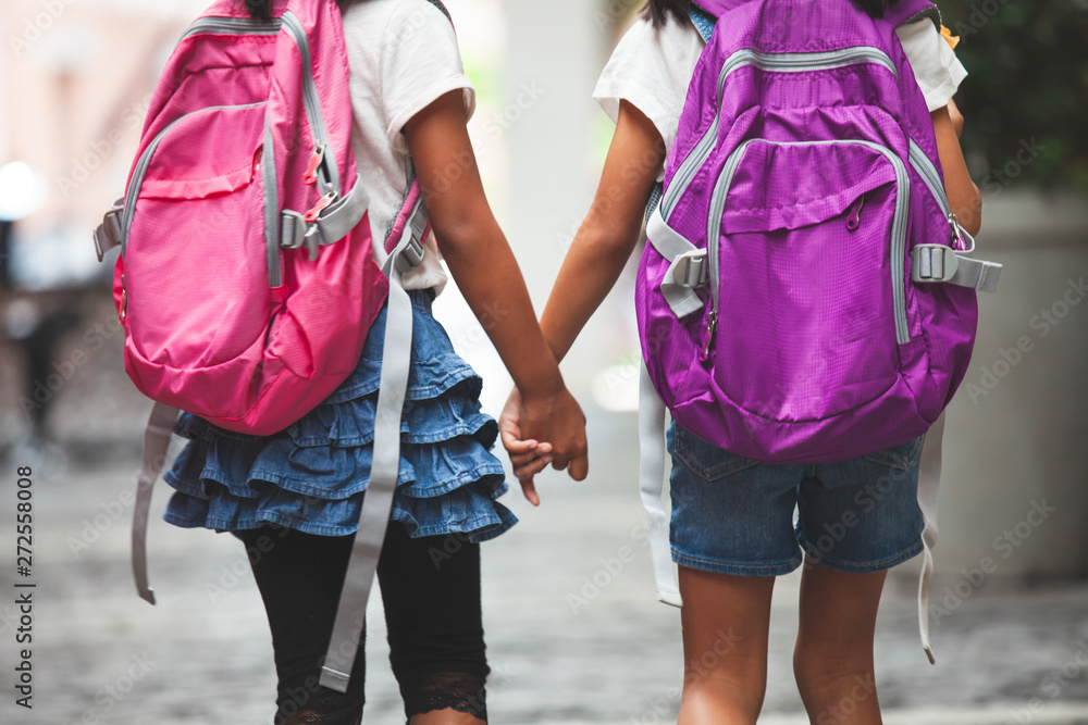 Fototapety, obrazy: Back to school. Two cute asian child girls with school bag holding hand and walk together in the school
