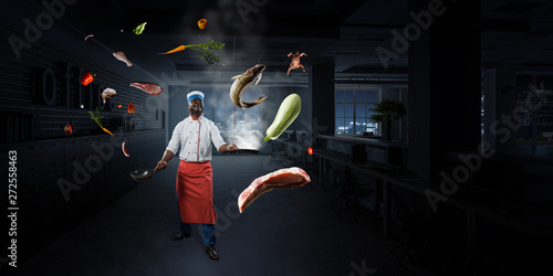 Fotografie, Obraz  Black man wearing an apron and cooking in action. Mixed media