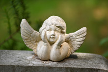 A Little White Angel With Spread Wings On A Tombstone.