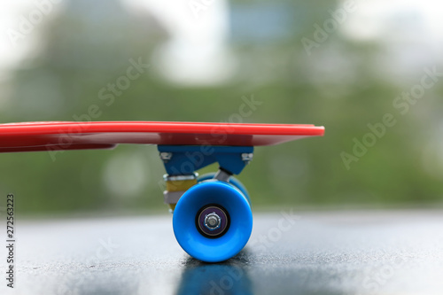 Red skateboard ready for riding at city