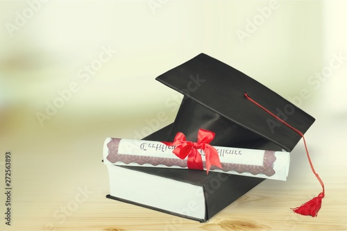 Fotografía Graduation hat with book and diploma on wooden desk