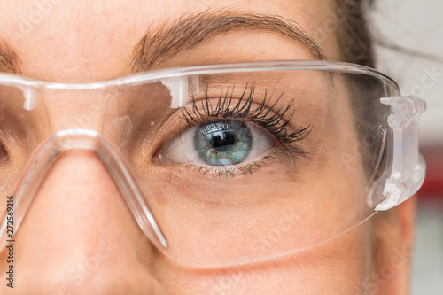 Fotografía  A beautiful young Caucasian is viewed closeup in the workplace, wearing protective goggles over her eyes
